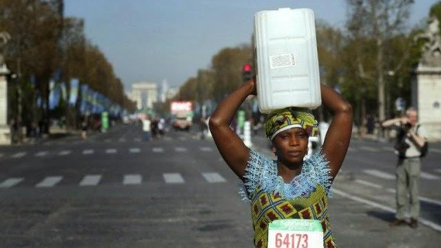Una mujer recorre una maratón con un bidón de agua en la cabeza